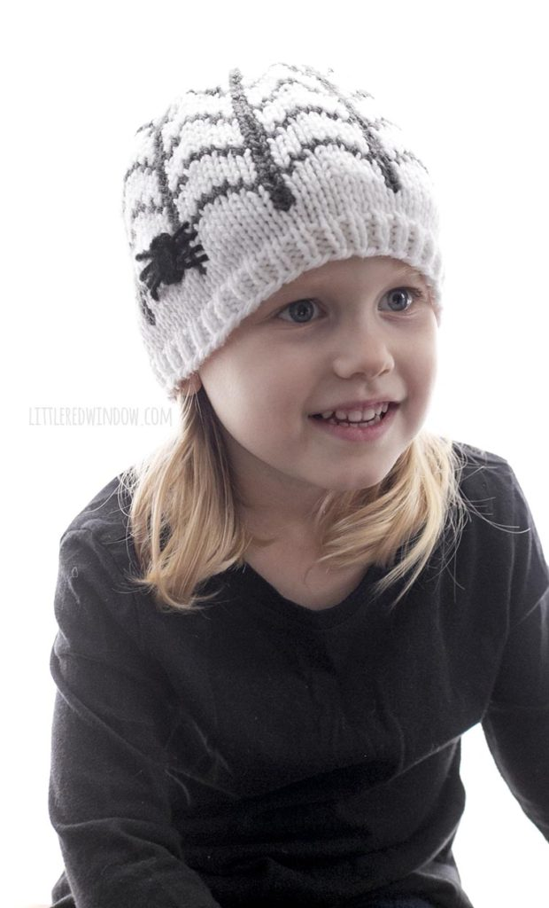 Little girl smiling and wearing a white knit hat with spiderweb pattern and spider applique on the side