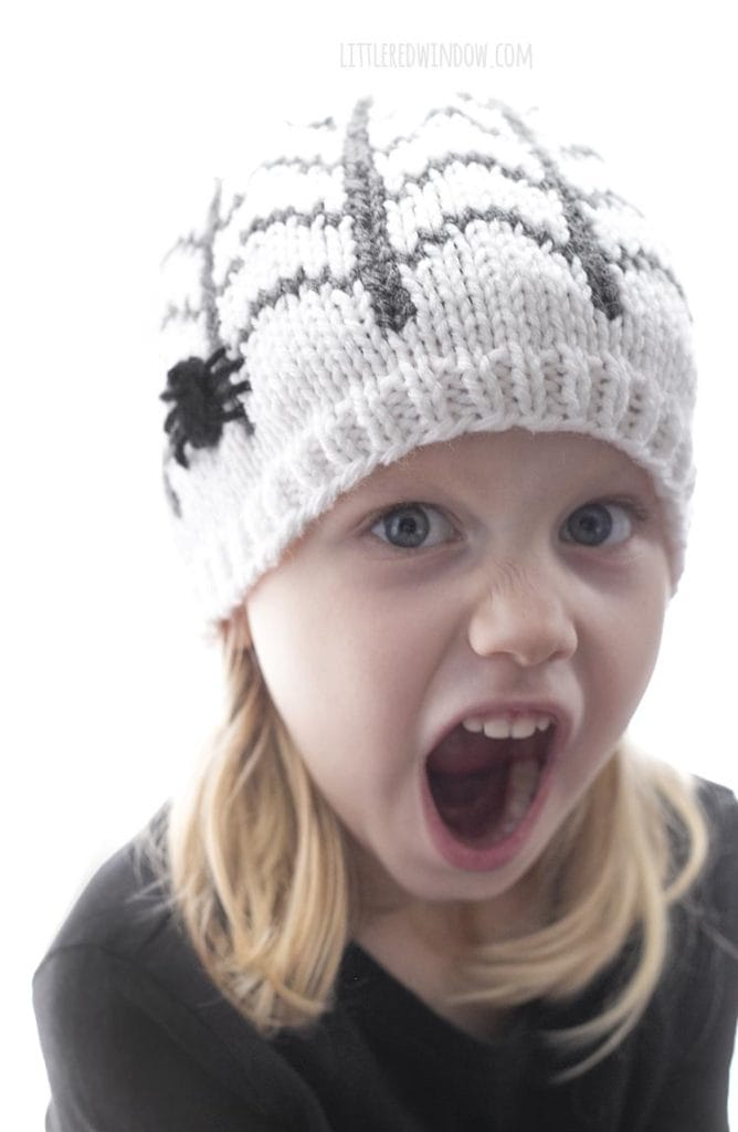 Little girl making surprised face and wearing a white knit hat with spiderweb pattern and spider applique on the side
