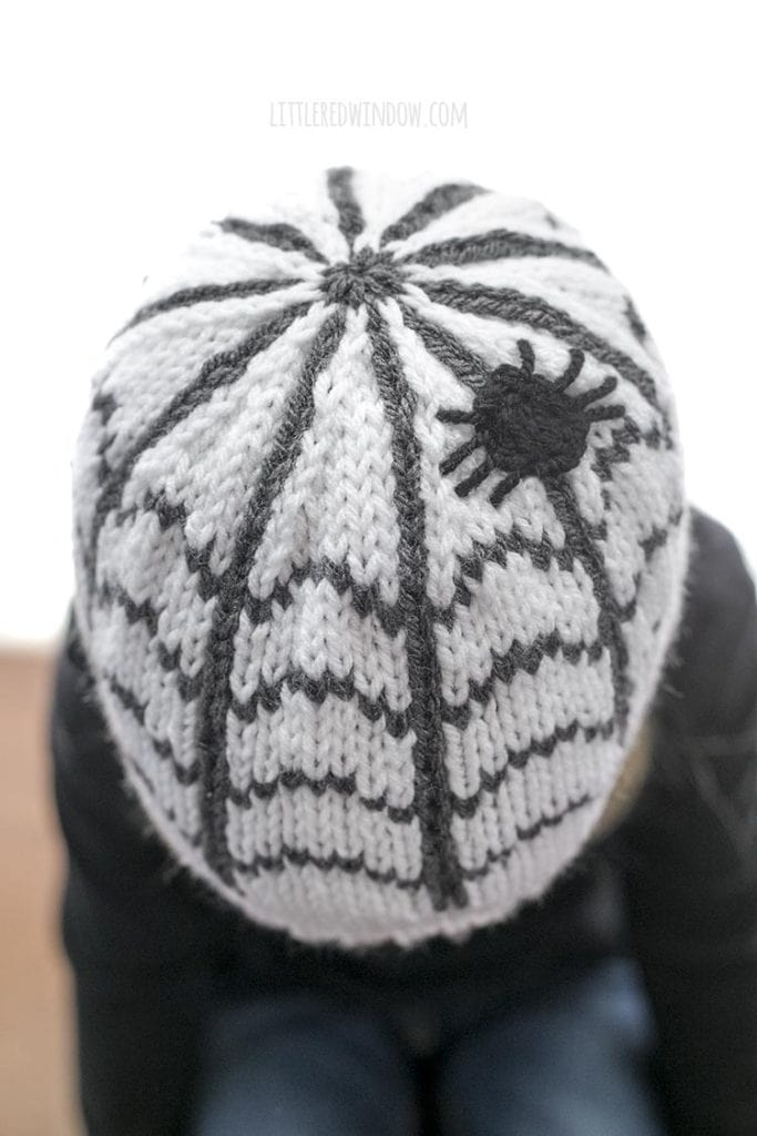 Top view of Little girl looking down wearing a white knit hat with a spiderweb pattern and a spider on the top