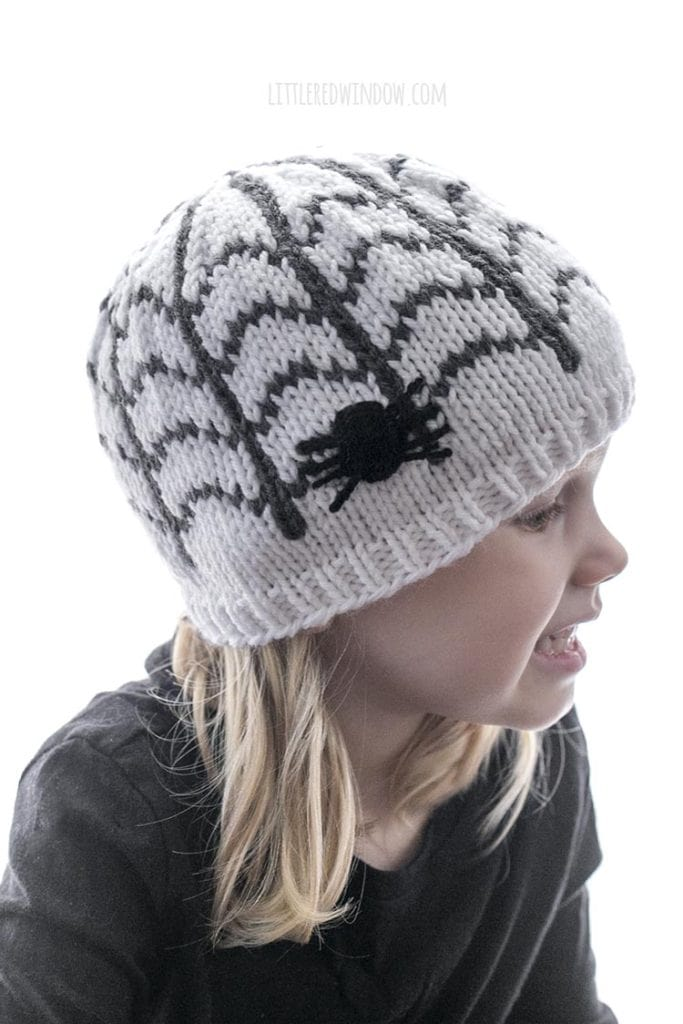 Little girl looking to the right wearing spiderweb patterned hat with a spider on the side