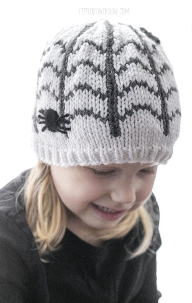 Little girl looking down and right wearing spiderweb patterned hat with a spider on the side