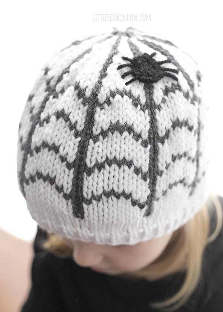 Little girl looking down wearing a white knit hat with a spiderweb pattern and a spider on the top
