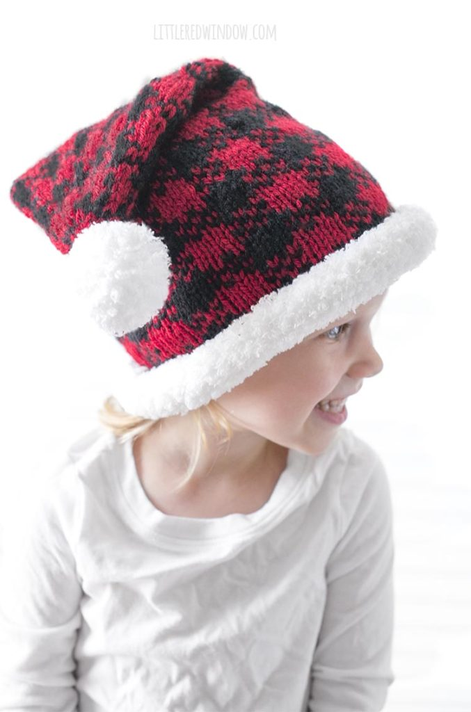 little girl wearing red and black buffalo plaid santa hat and looking off to the right