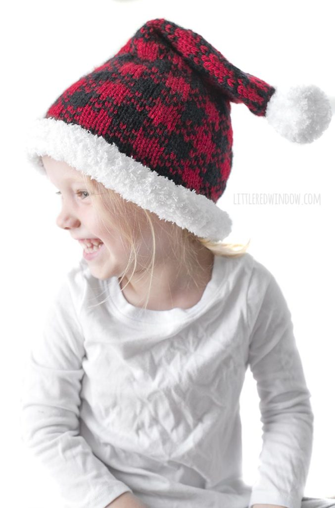 little girl wearing red and black buffalo plaid santa hat and looking off to the left