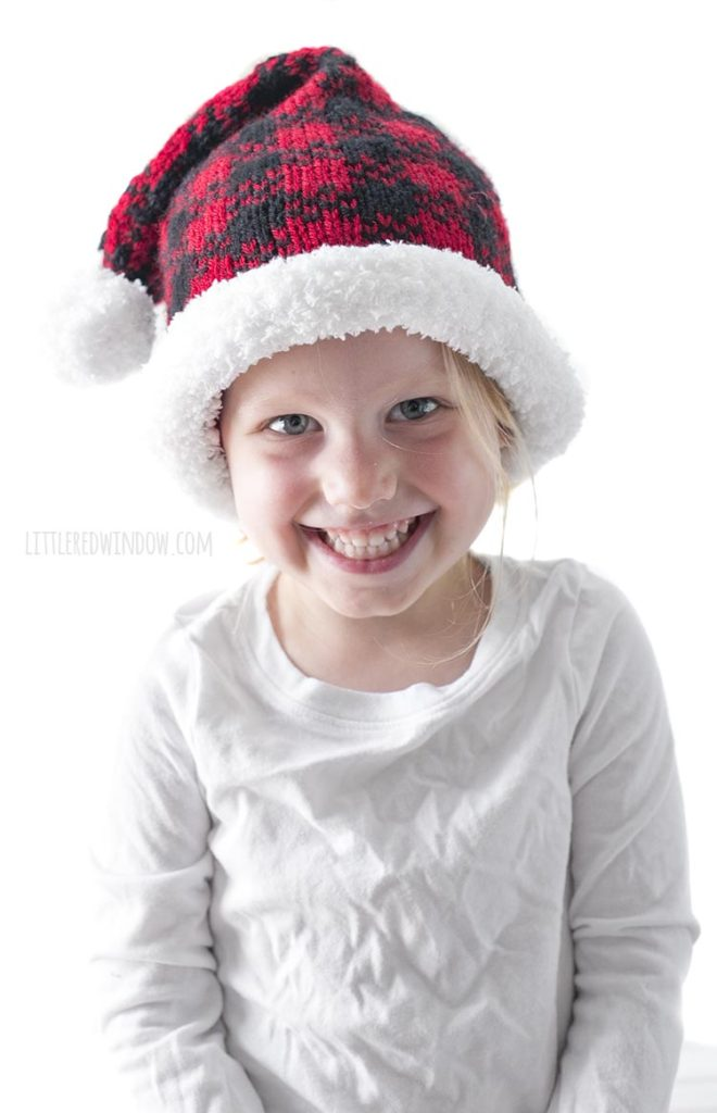 smiling girl wearing red and black plaid santa hat and white shirt