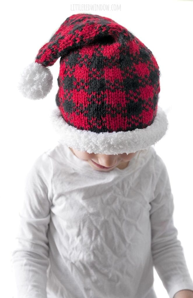 little girl looking down and wearing a red and black buffalo plaid santa hat
