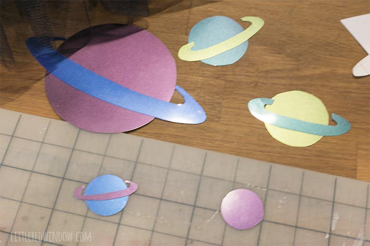 planet shapes cut out of metallic heat transfer vinyl in purple blue green and yellow for an outer space costume