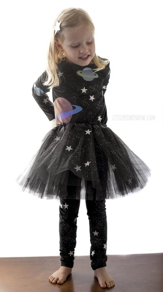 little girl standing up wearing all black outfit with stars and planets on it as an outer space costume