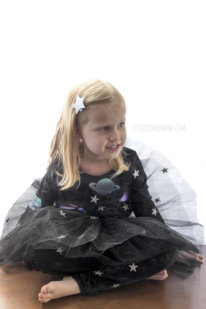 little girl sitting down wearing all black outfit with stars and planets on it as an outer space costume