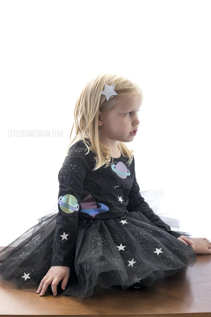 little girl sitting down and looking off to the rightwearing all black outfit with stars and planets on it
