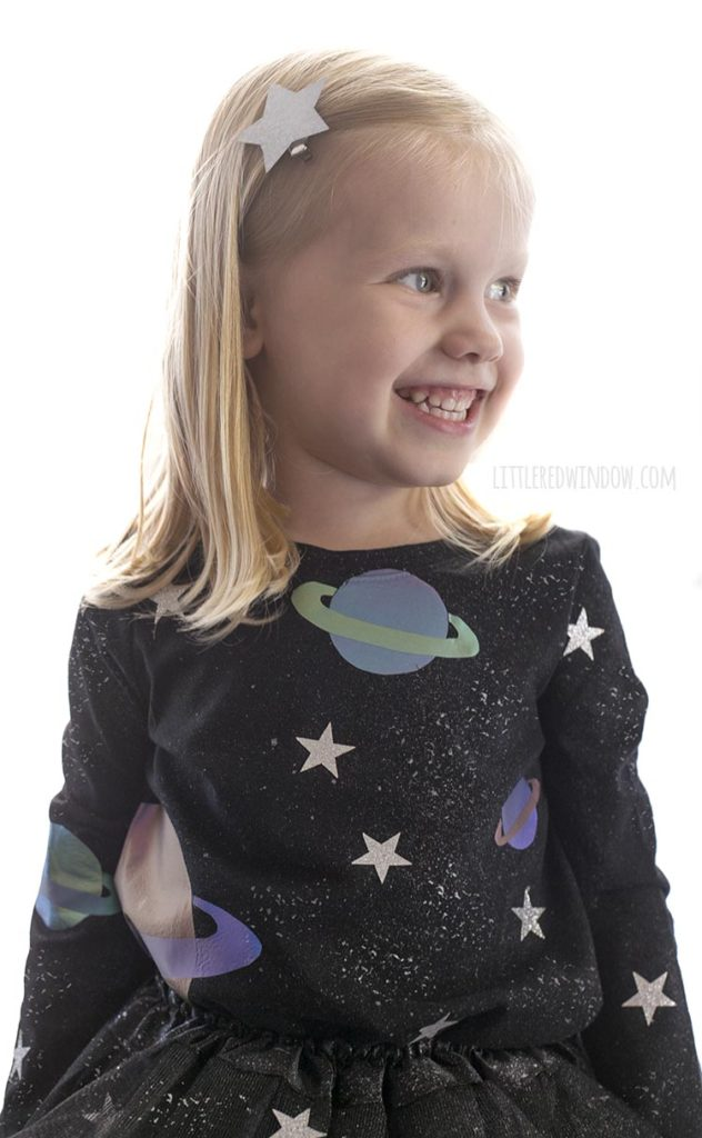 closeup of smiling girl wearing black shirt with stars and planets on it for her outer space costume