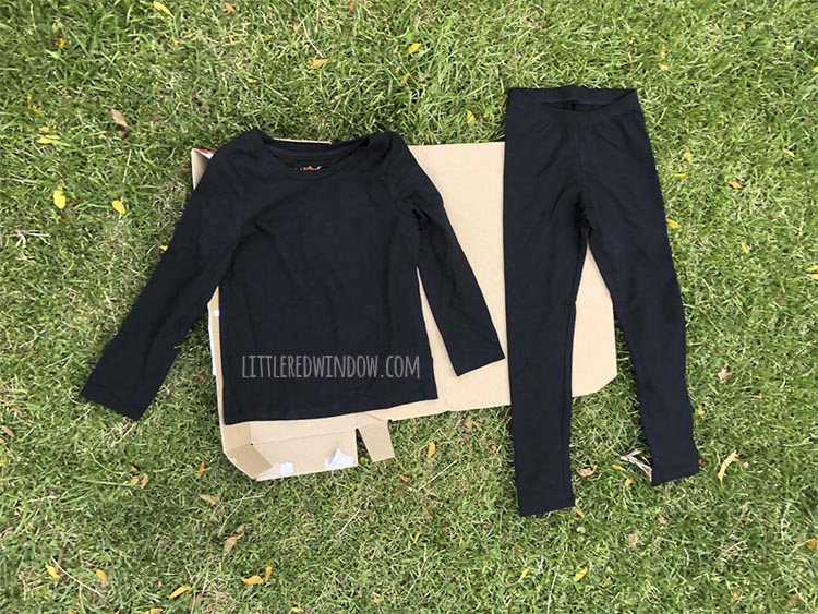 black toddler shirt and pants for an outer space costume laying on cardboard on top of grass