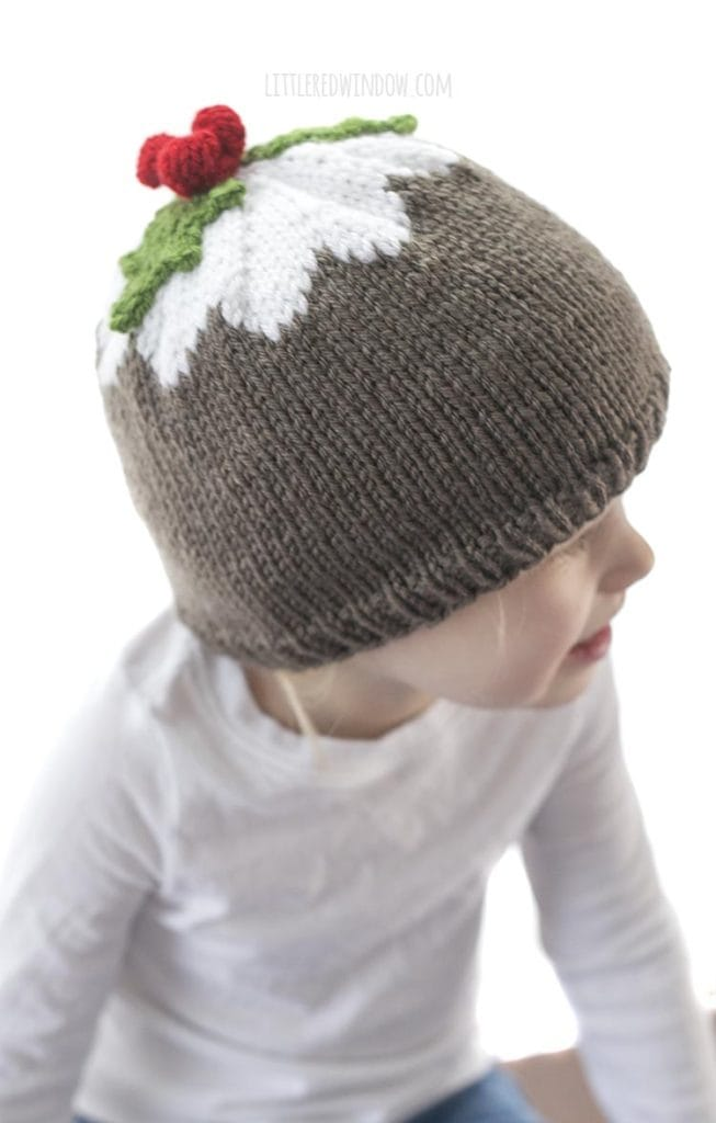 little girl wearing brown and white figgy pudding hat with green leaves and red berries on top looking off to the right