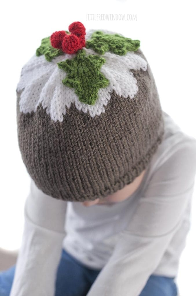 little girl wearing brown and white figgy pudding hat with green leaves and red berries on top looking down to the left