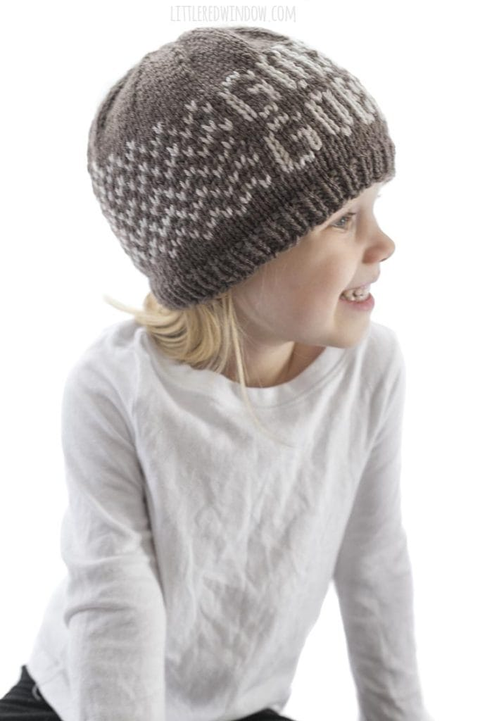 little girl wearing brown knit gobble gobble hat smiling and looking off to the right