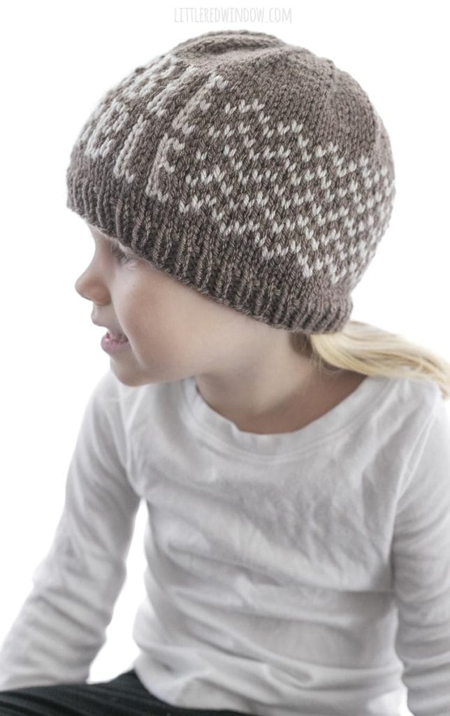 side view of girl wearing brown knit hat with gobble gobble pattern on front and zig zag pattern around the sides