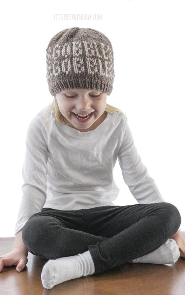 little girl sitting cross legged and wearing black pants white shirt and brown knit hat that says gobble gobble on the front