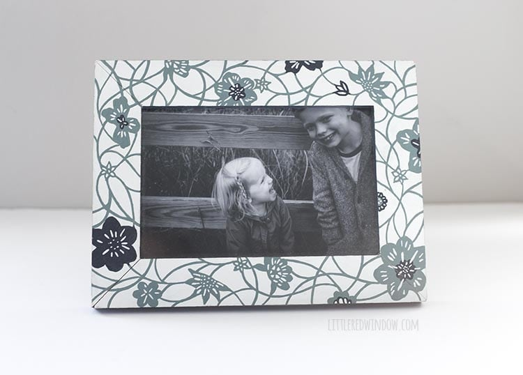Closeup of a black and white photo of two kids in a teal and white floral frame