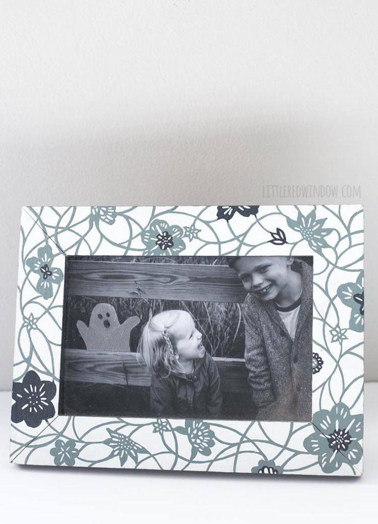 Floral picture frame holding a black and white photo of two kids with a transparent ghost popping up from behind a fence behind them