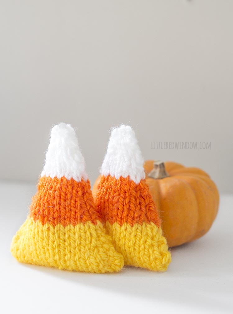 two knit camdy corn handwarmers propped up against a mini pumpkin