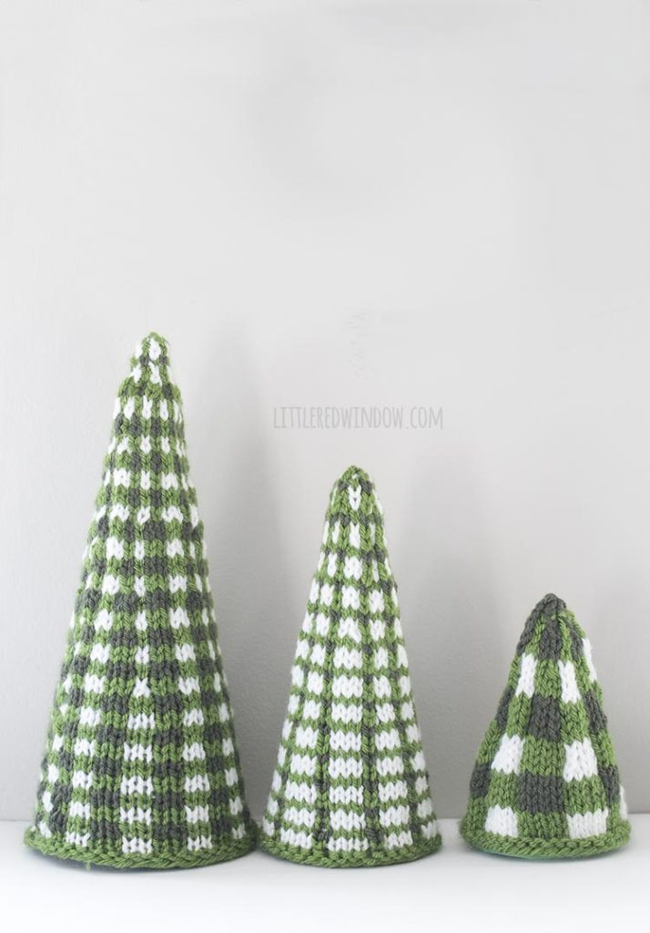 Three green and white plaid knit Christmas tree shapes in a line from large to small