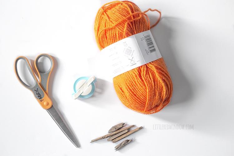 orange yarn scissors pom pom maker and sticks on a white background