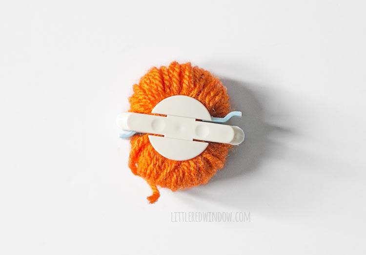 pom pom maker wound with orange yarn