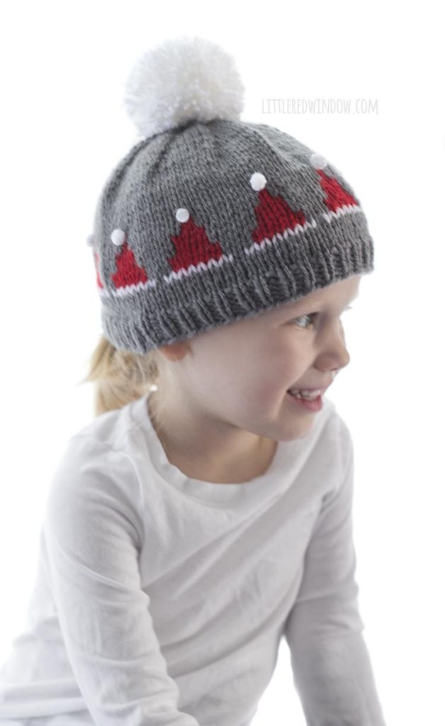little girl wearing gray knit hat with small red santa hats on it and looking off to the right