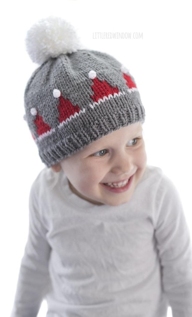 smiling little girl wearing gray knit hat with small red santa hats on it and looking off to the right
