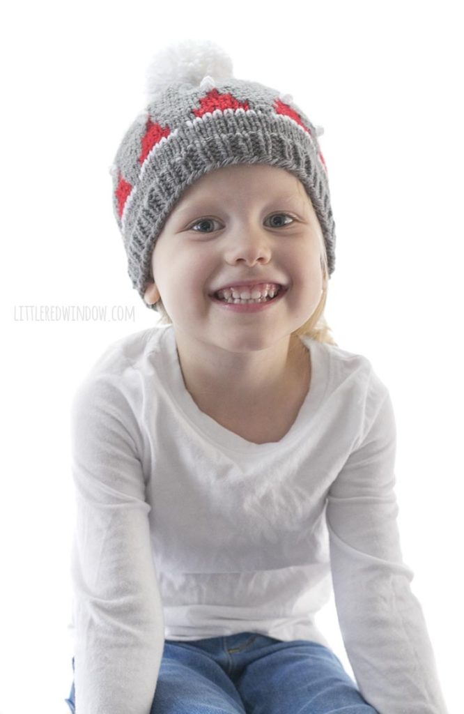 Smiling little girl in white shirt wearing gray knit hat with red santa hats on it and a white pom pom on top