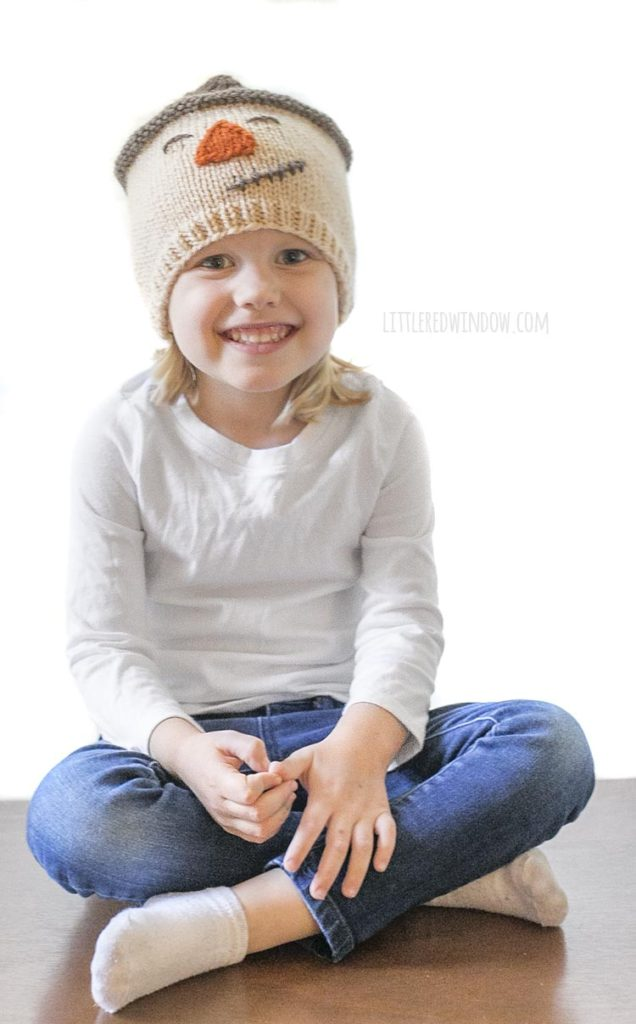 little girl in white shirt smiling and wearing knit scarecrow hat