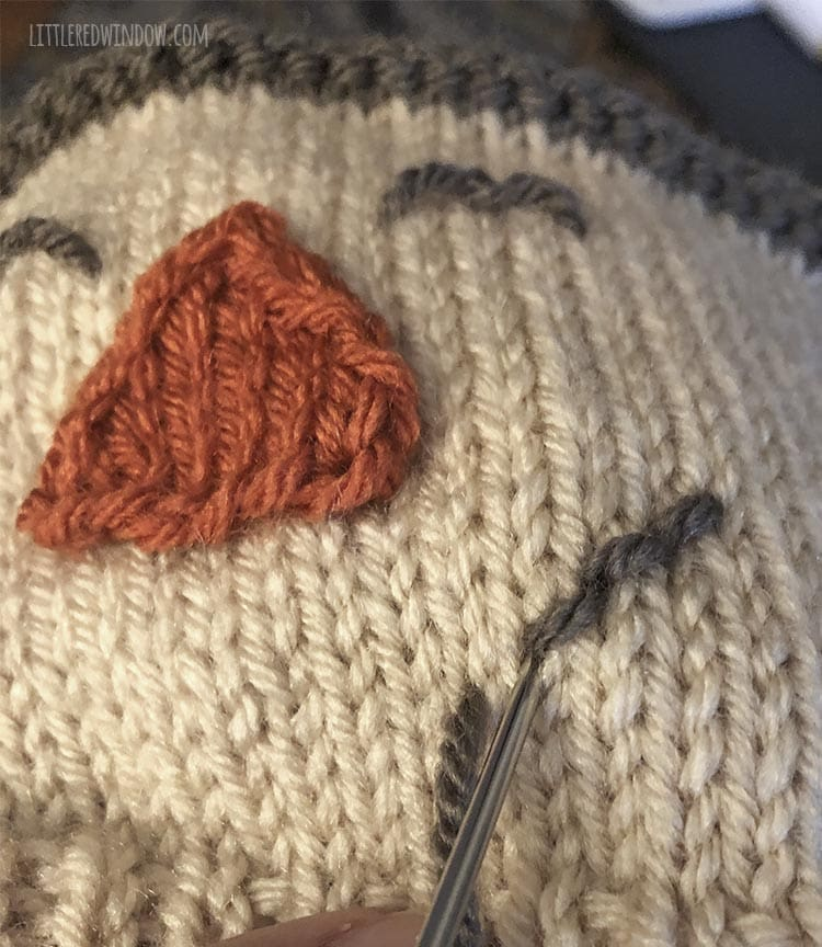 closeup of yarn needle using backstitch to stitch the smile on the scarecrow hat