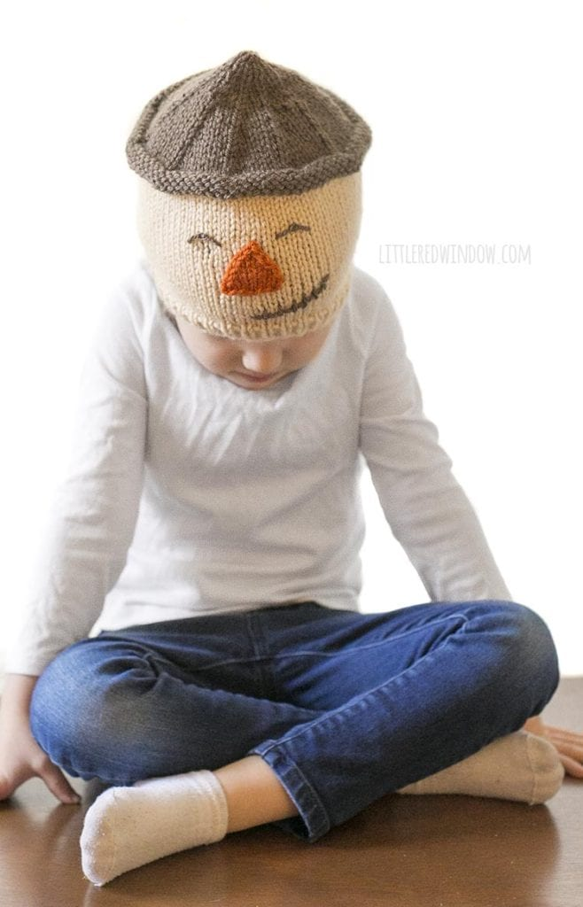 little girl looking down and wearing a tan knit hat with a scarecrow face on it
