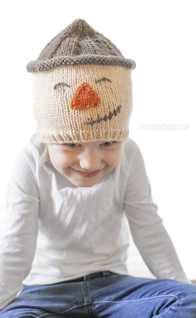 little girl laughing and wearing a scarecrow hat