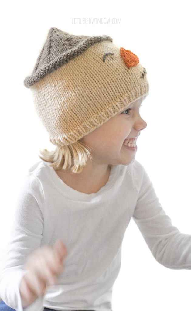 little girl wearing scarecrow hat and looking off to the right