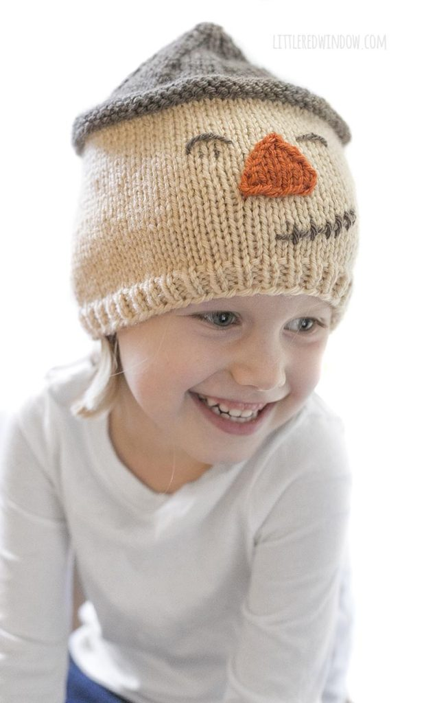 little girl smiling and wearing smiling scarecrow hat