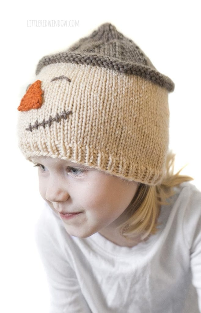 little girl wearing scarecrow hat and looking off to the left