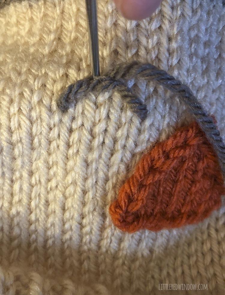 closeup of yarn needle stitching scarecrow eye with brown yarn