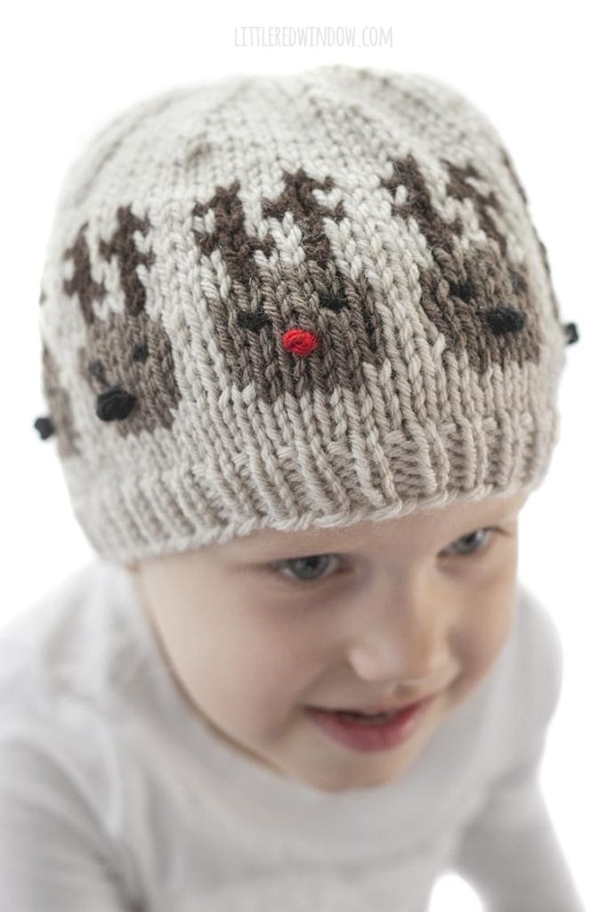 closeup of little girl wearing team of reindeer hat showing one reindeer with a red nose