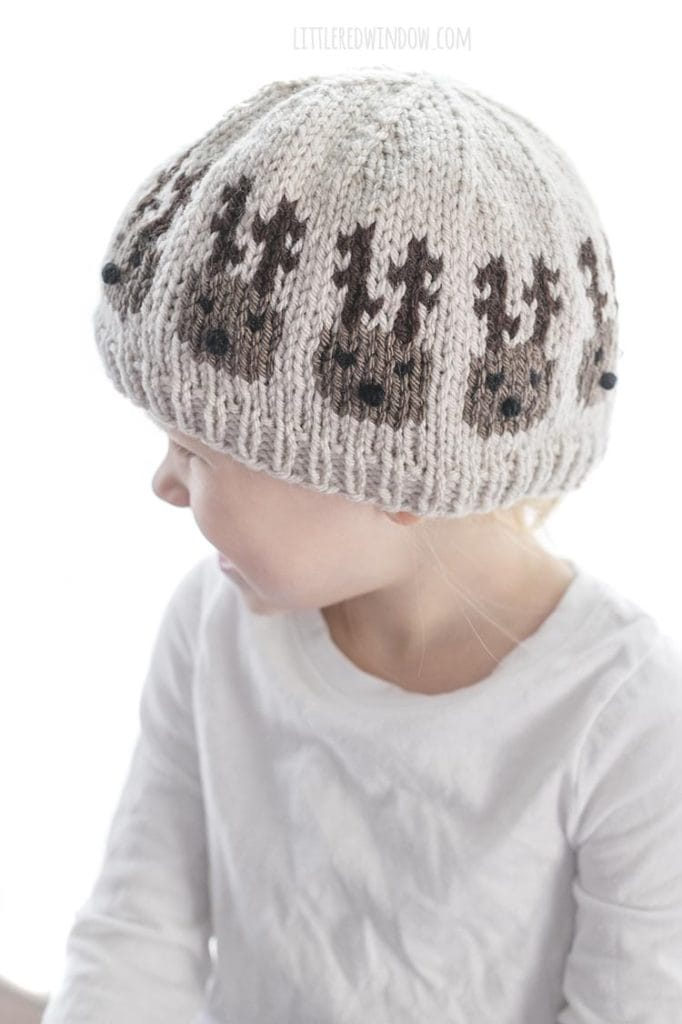 little girl wearing knit hat with team of reindeer around the middle