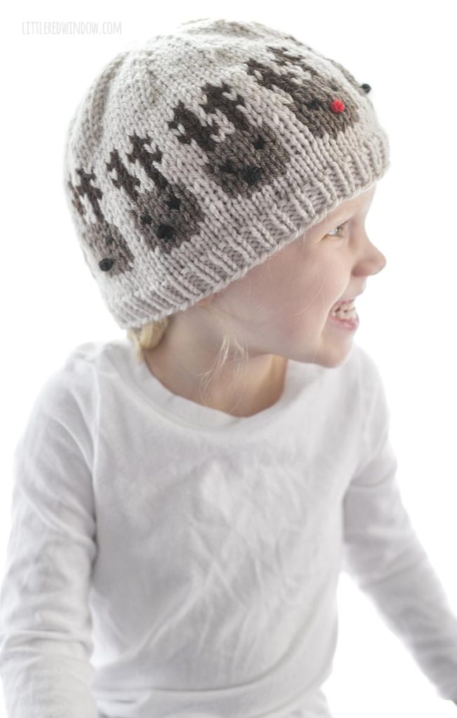 little girl wearing tan knit hat with reindeer heads around the middle looking off to the right