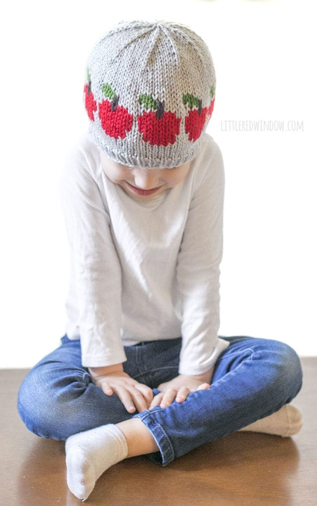 Little girl sitting down and wearing gray knit hat with red apples around the middle