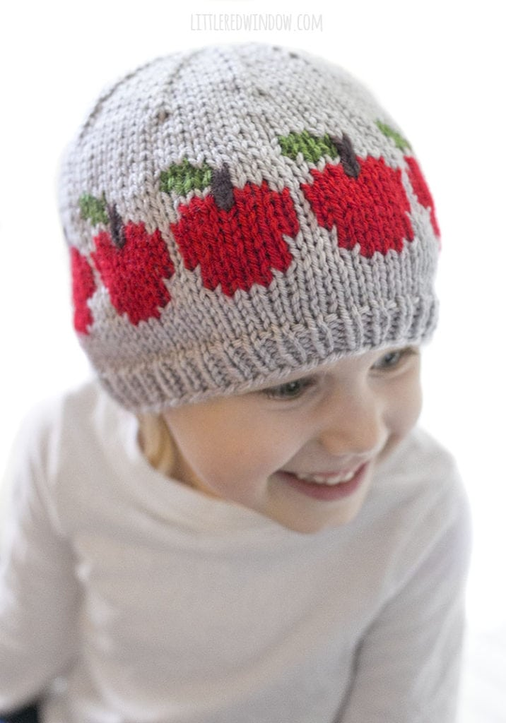 little girl smiling and wearing gray hat with red apples on it