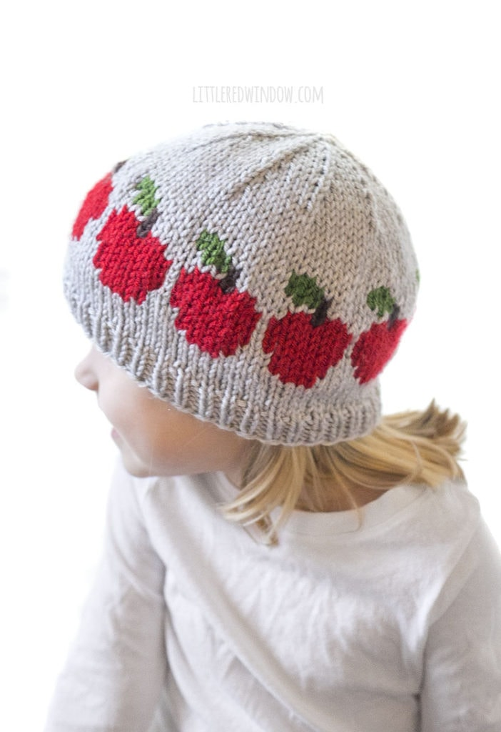 little girl wearing freshly picked apple hat looking off to the left