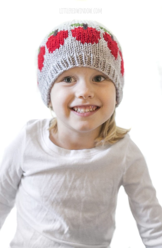 little girl in white shirt smiling and wearing gray knit hat with a row of red apples on it