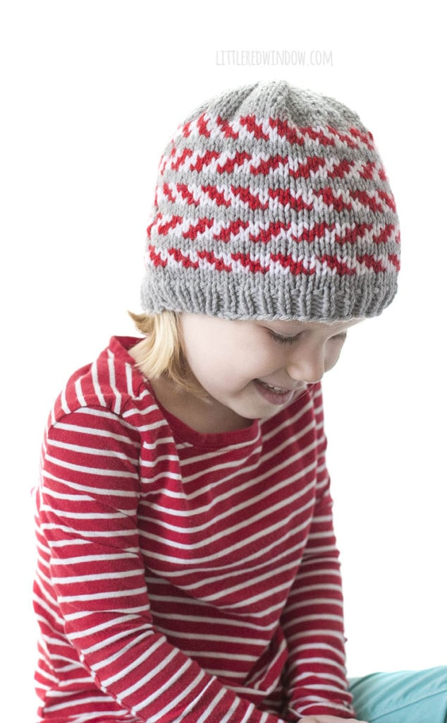 little girl and a red striped shirt wearing a gray knit hat with red and white candy cane stripes and looking down to the right