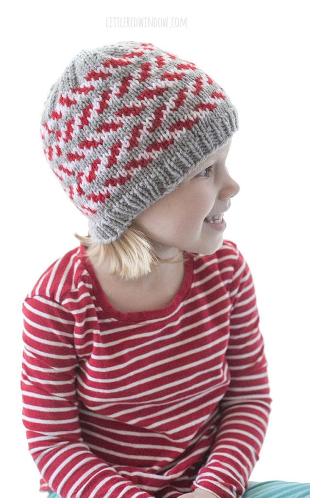 little girl and a red striped shirt wearing a gray knit hat with red and white candy cane stripes and looking off to the right