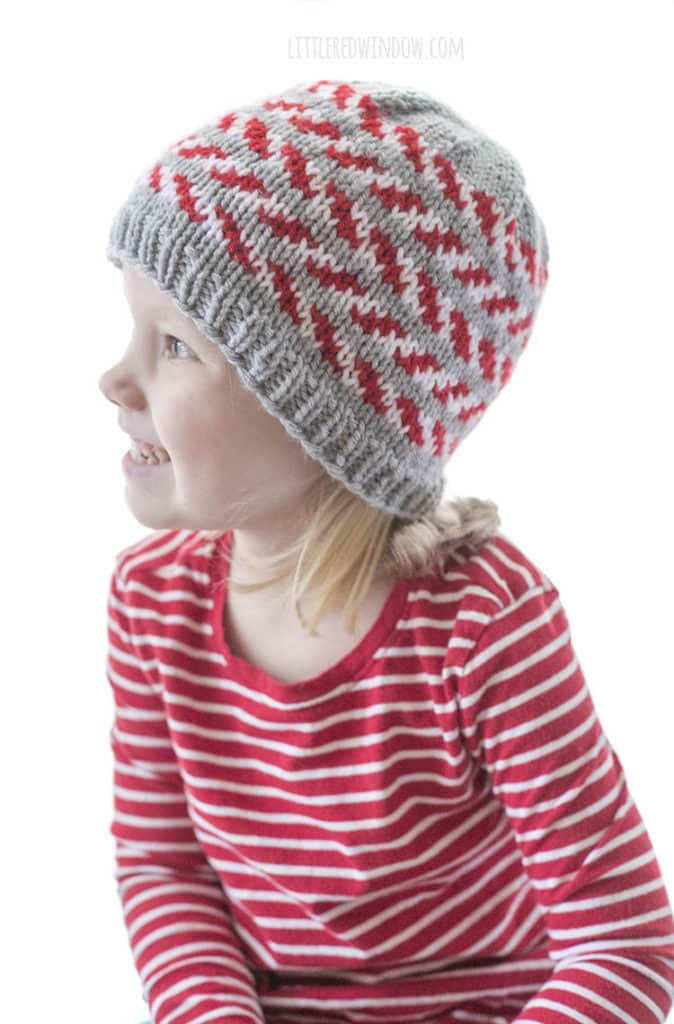 little girl and a red striped shirt wearing a gray knit hat with red and white candy cane stripes and looking off to the left