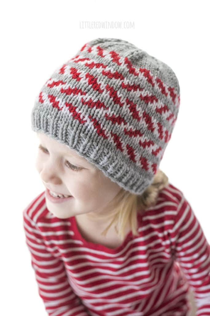 little girl and a red striped shirt wearing a gray knit hat with red and white candy cane stripes and looking down to the left