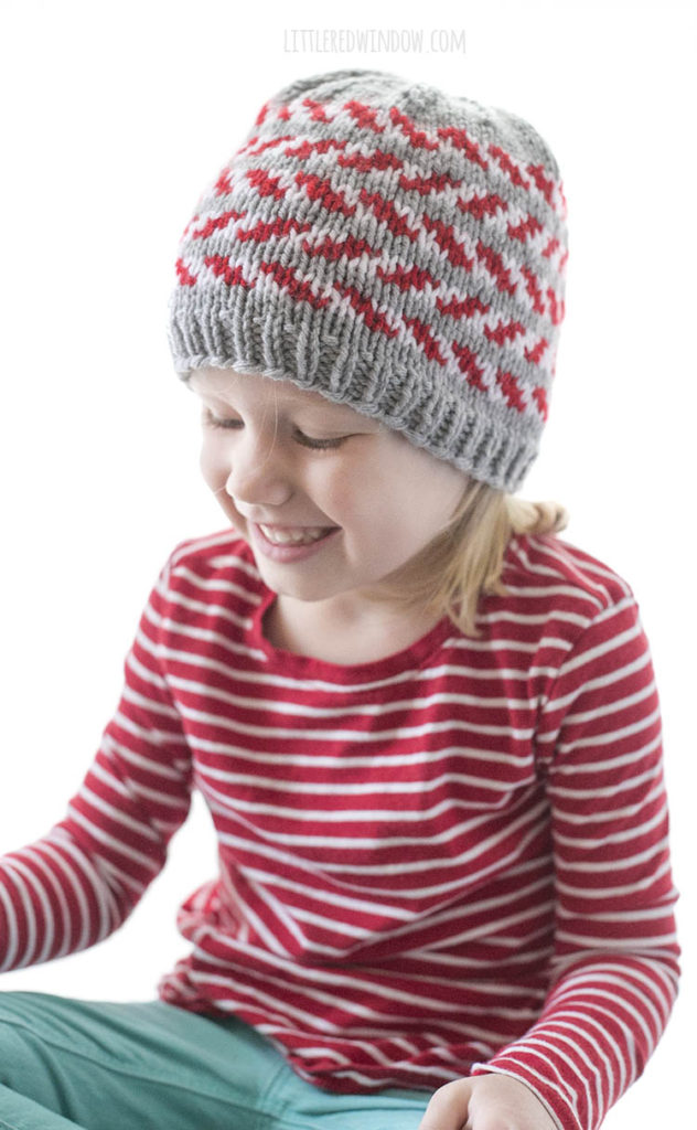 little girl and a red striped shirt wearing a gray knit hat with red and white candy cane stripes and looking down to the front